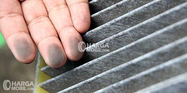 Tangan seorang berdebu setelah memeriksaFilter Kabin Kotor