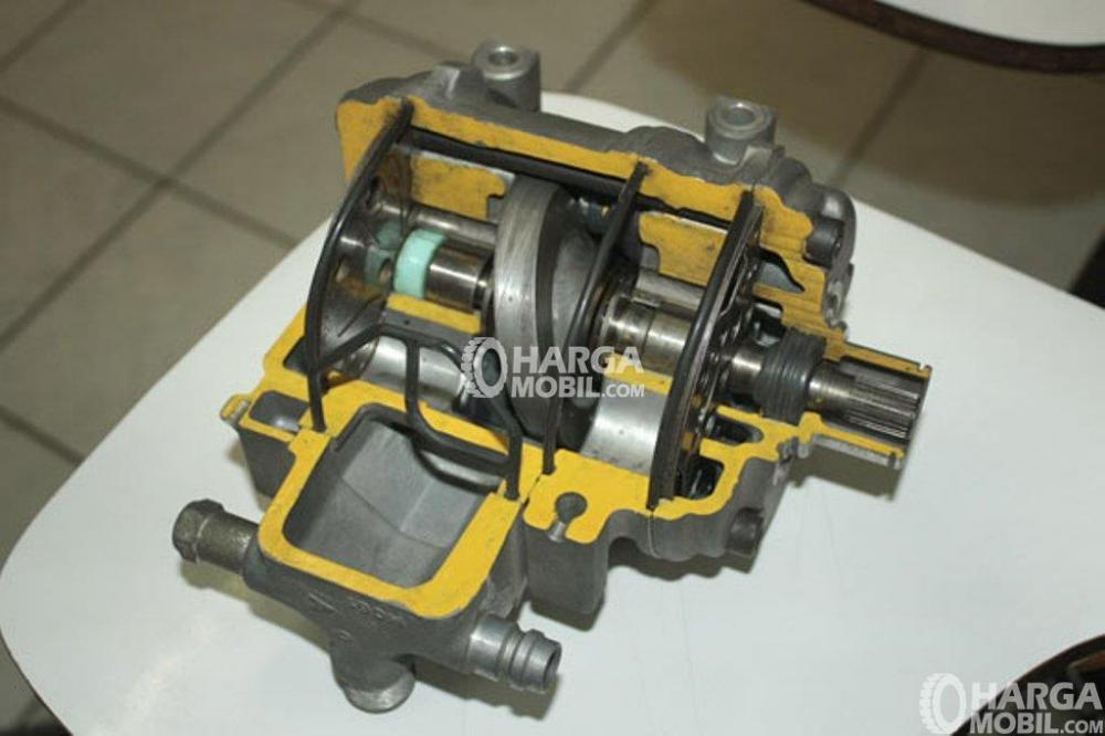 Sebuah kompressor AC mobil berwarna silver dan kuning yang hadir di meja