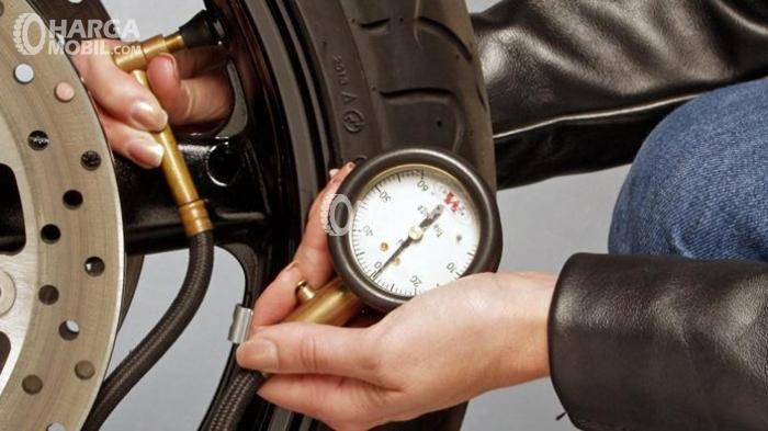 Seorang pria sedang mengecek tekanan ban mobil dengan alat ukur saat mengisi angin