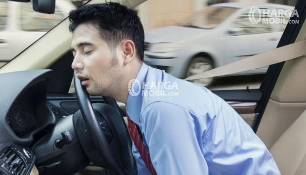 Seorang pria sedang tidur sangat nyenyak dalam sebuah kursi depan mobil