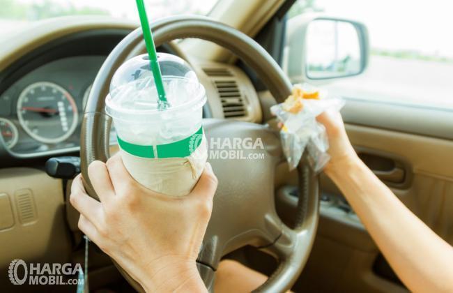 gambar seorang sedang mengemudi sambil memegang hambuger dan minumannya