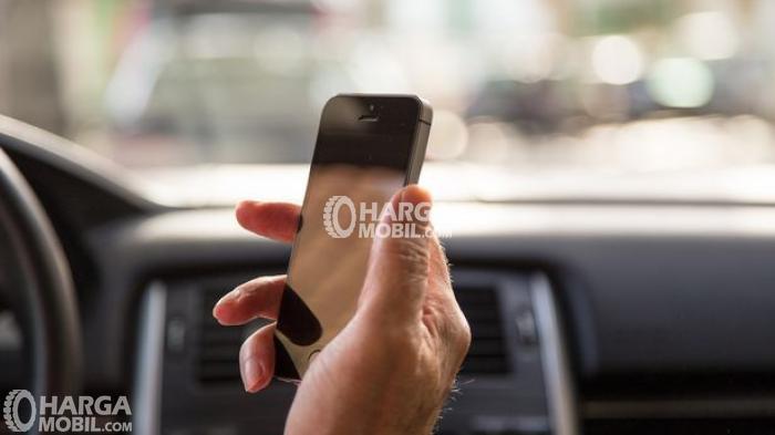 Gambar seorang sedang menggunakan ponsel Iphone jika mengemudi