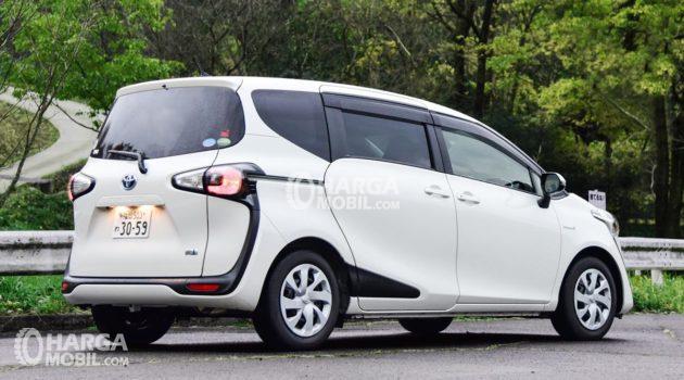 Model Toyota Sienta varian bensin sedang dipasarkan di Indonesia berwarna putih sedang pakir di pinggir jalan