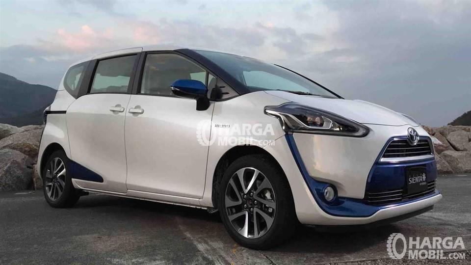 Model toyota Sienta Hybrid sedang dipelajari untuk cocok dengan kondisi di Indonesia berwarna silver sedang pakir di sebuah jalan yang tinggi