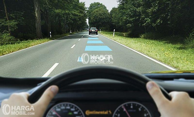 seorang pria sedang mengendarai mobilnya menjaga jarak dengan kendaraan di depannya