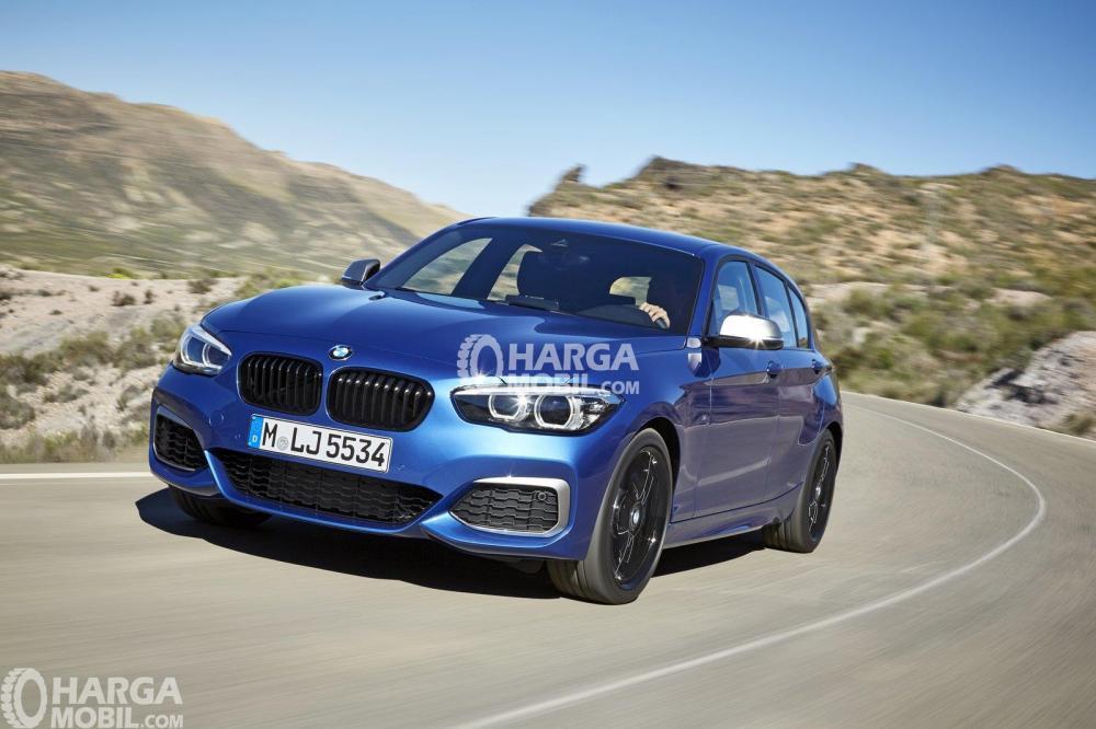 Gamabr mobil BMW Seri 1 berwarna biru dilihat dari bagian depan sedang naik gunung