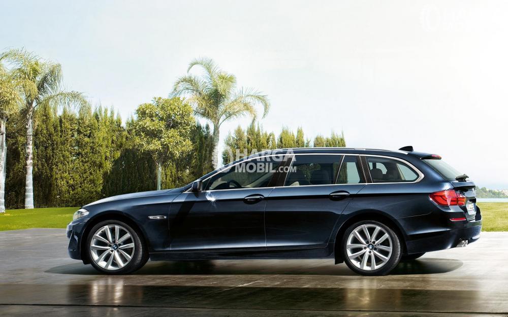 Gambar mobil BMW Seri 6 berwarna hitam dilihat dari bagian samping sedang parkir di depan taman mini Indonesia