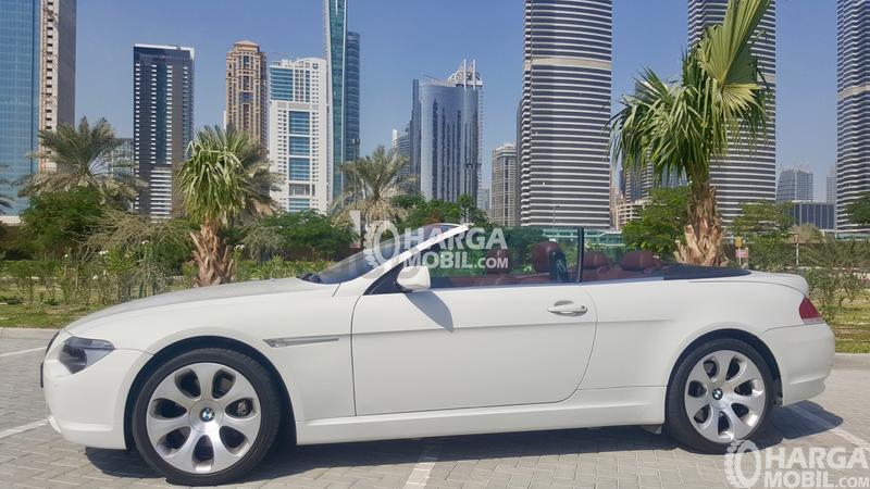 MObil BMW Seri 6 berwarna putih dilihat dari bagian depan sedang parkir di depan gedung yang mewah