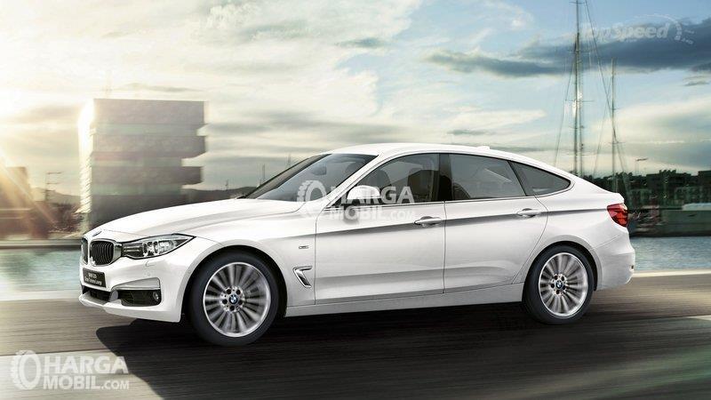 Mobil BMW Seri GT berwarna putih dilihat dari bagian samping sedang di jalan raya Indonesia