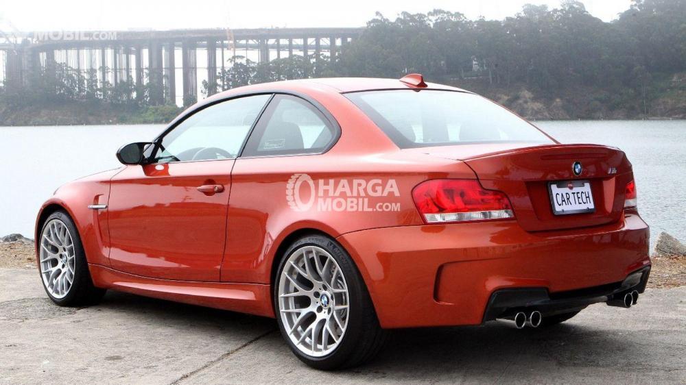 Mobil BMW Seri M berwarna merah dilihat dari bagian belakang sedang parkir di depan sebuah sungai di Indonesia