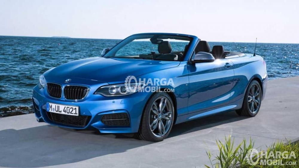 Mobil BMW seri 2 berwarna biru sedang parkir di depat pantai di Indonesia