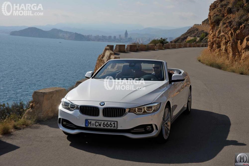 Mobil BMW Seri 4 berwarna putih dilihat dari bagian depan sedang berjalan di jalan yang dekat pantai