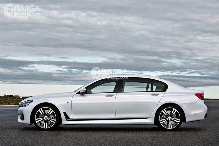 Mobil BMW Seri 7 berwarna putih dilihat dari bagian depan sedang parkir di dekat pantai