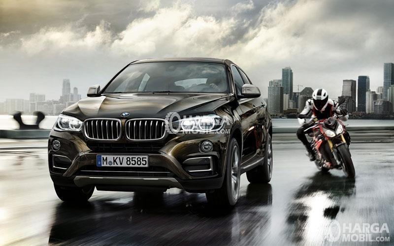 Mobil BMW Seri X berwarna hitam sedang di jalan dan di sebelah kanan ada sebuah motor jalan di sampingnya