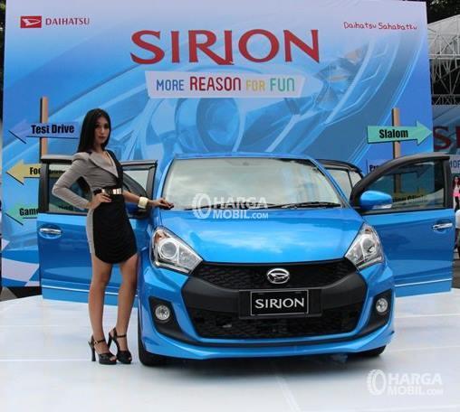 Gambar mobil Daihatsu Sirion berwarna hitam sedang parkir di samping model yang memakai rok berwarna abu-abu