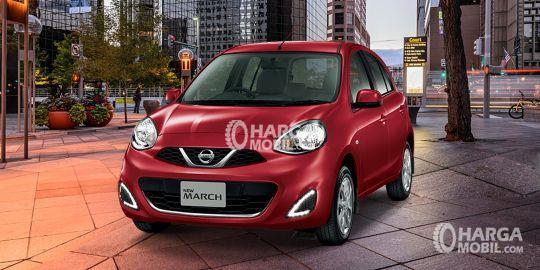 Mobil Nissan March berwarna merah dilihat dari bagian depan sedang parkir di depan warung makan yang indah pada malam hari