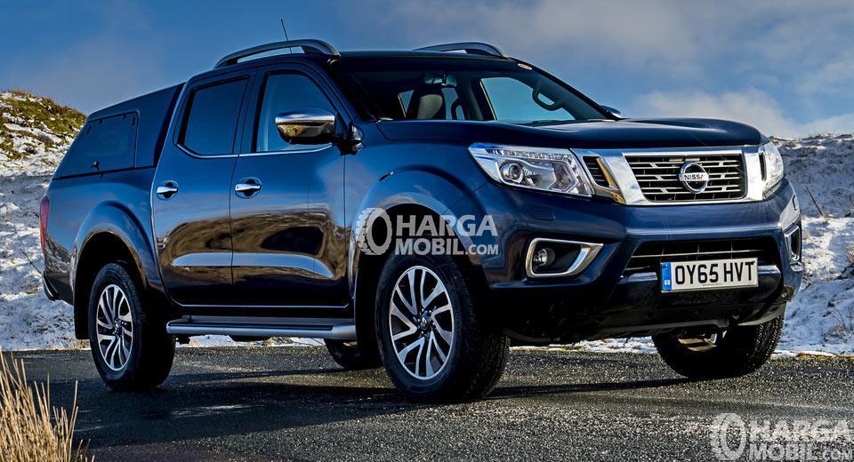 mobil Nissan Navara berwarna biru tua dilihat dari bagian depan