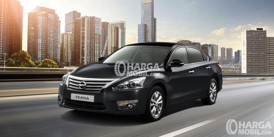 Mobil Nissan Teana berwarna hitam sedang parkir di tengah jalan