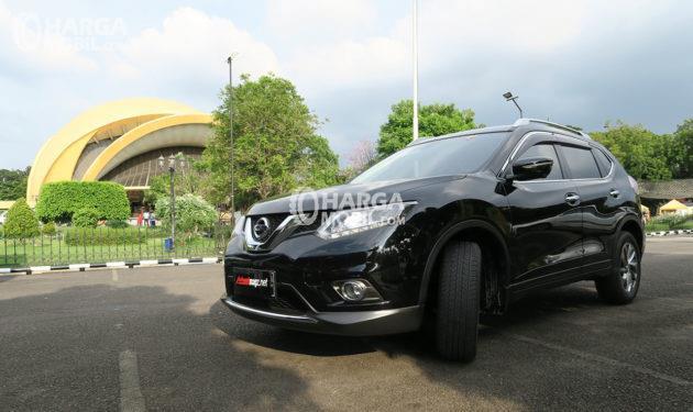 Mobil Nissan X-Trail berwarna hitam dilihat dari bagian depan sednag parkir di taman wisata di Indonesia