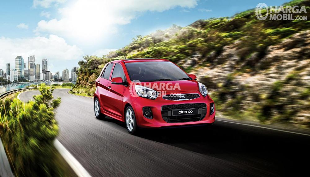 Mobil Kia Picanto berwarna merah dilihat dari bagian depan sedang berjalan di jalan