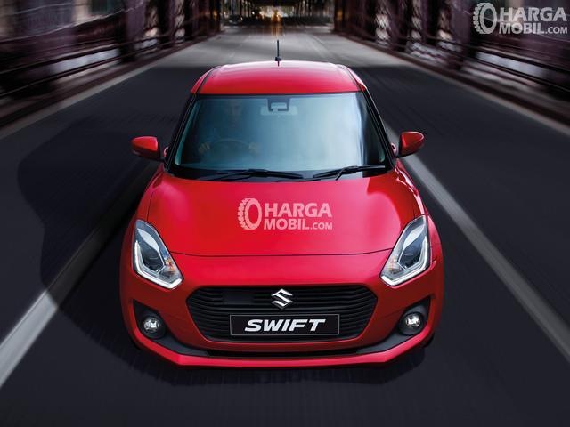 Mobil Suzuki Swift berwarna merah dilihat dari bagian depan sedang berjalan di jalan raya