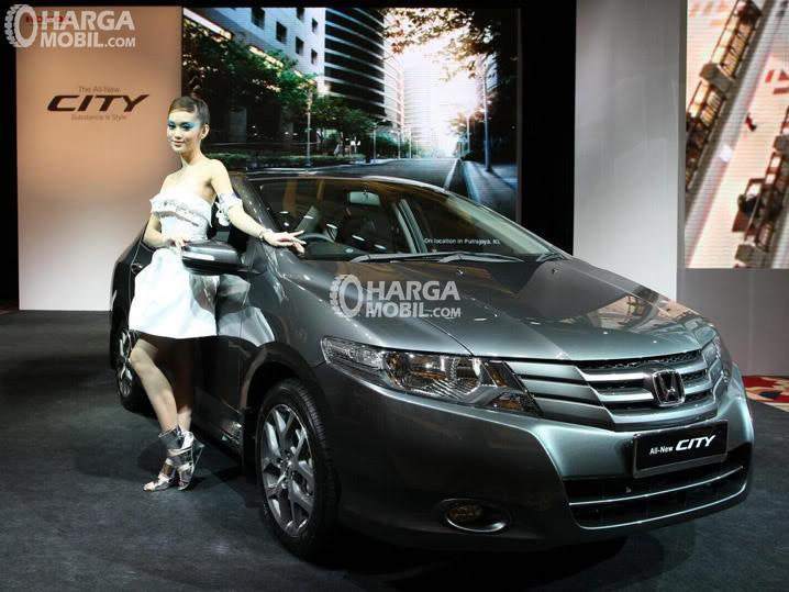 sebuah mobil Honda City berwarna abu - abu hitam hadir di pameran dan seorang wanita duduk di sampingnya