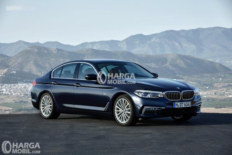 sebuah mobil sedan BMW 5 Series berwarna hitam sedang diparkir di pinggir jalan