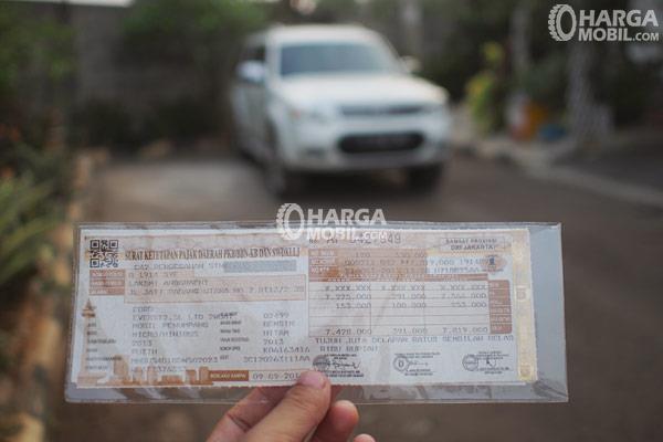 seorang sedang memegang sebuah dokumen surat ketetapan pajak daerah ditutupi dengan plastik