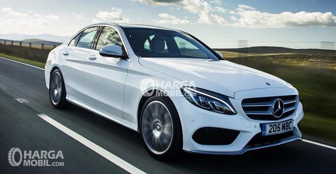 sebuah mobil Mercedes Benz berwarna silver sedang berkendara di jalan