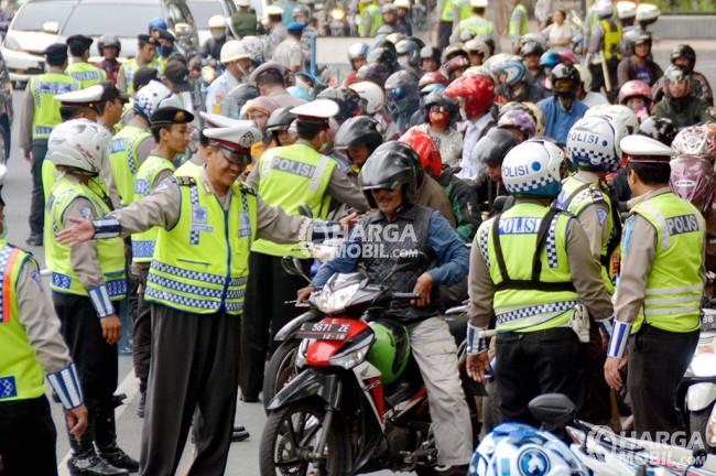 Seorang polisi mengemudikan seorang sopir sepeda motor untuk pergi