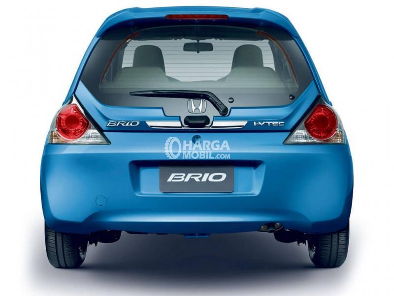 sebuah mobil honda brio berwarna biru sedang diparkir di jalan