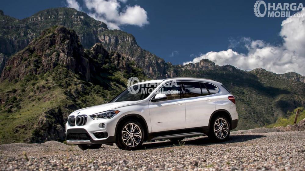 Mobil BMW X1 2016 berwarna putih dilihat dari sisi samping sedang parkir di dekat gunung di Indonesia