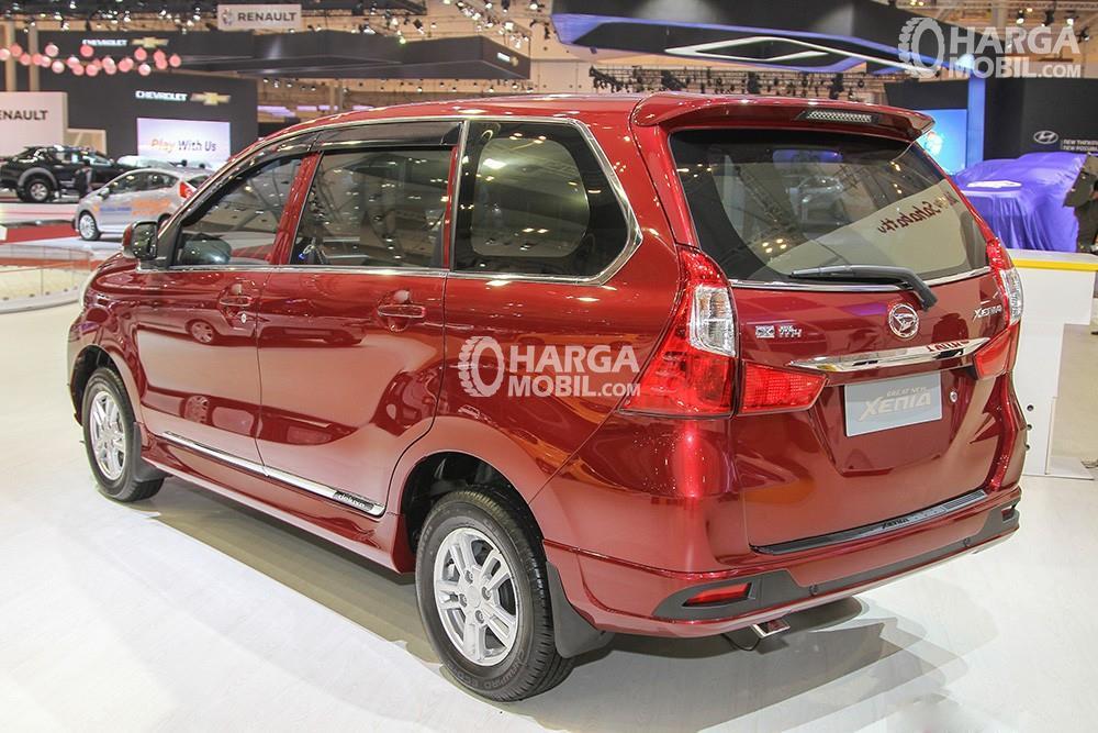 sebuah mobil MPV Daihatsu Xenia berwarna merah sedang hadir di sebuah pameran otomotif