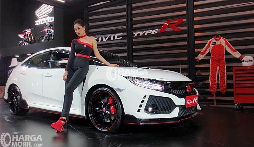seorang wanita sedang duduk di samping sebuah mobil honda civic type r berwarna merah sangat canggih