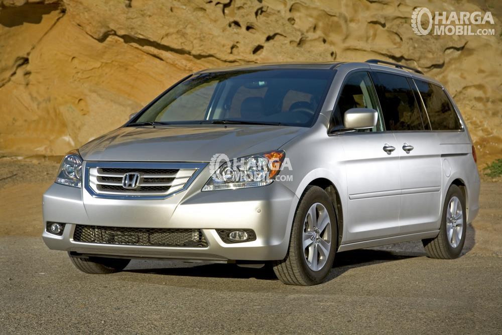 sebuah mobil MPV berwarna silver sedang diparkir di jalan dan sampingya ada gunungan