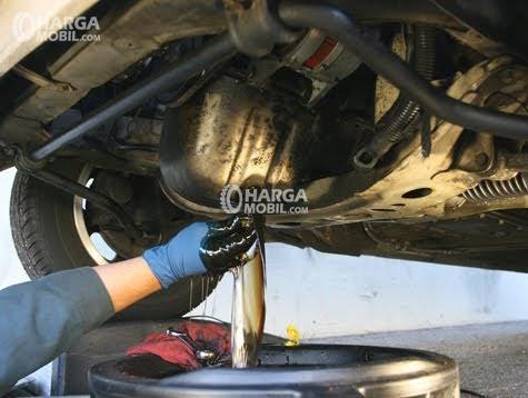 Seorang pria menggunakan tangannya untuk menghentikan oil agar tidak keluar dari mesin