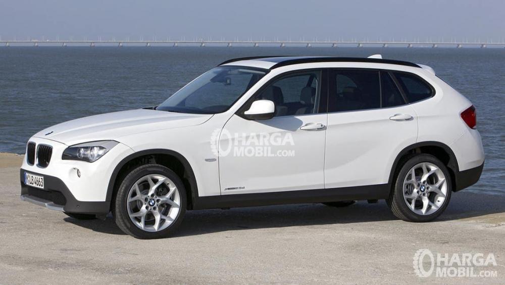 Tampilan bagian depan BMW X1 2012 berwarna putih sedang parkir di depan pantai yang indah
