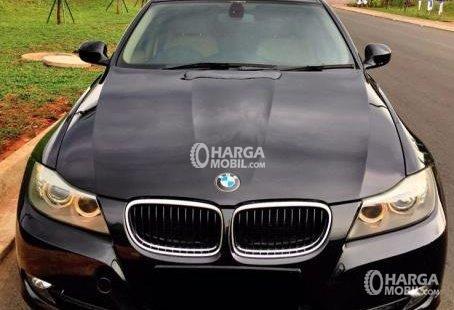 Gambar mobil BMW 320i 2010 berwarna hitam dilihat dari bagian depan