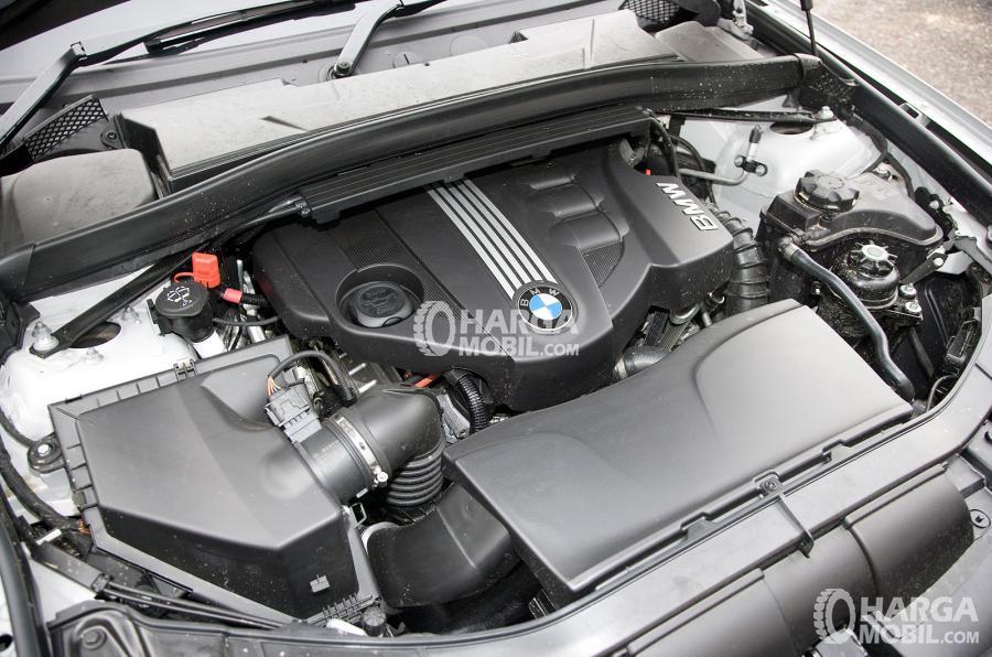 Gambar bagian mesin mobil BMW X1 2015 dengan logo BMW di tengah