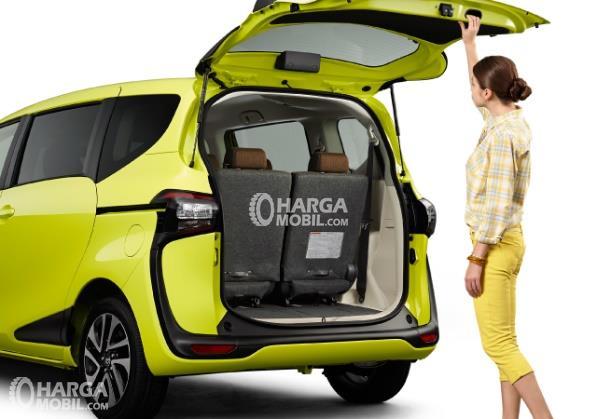 Gambar ruang bagasi mobil Toyota Sienta 2016 berwarna hijau muda dan seorang wanita sedang berbuka ruang bagasi itu