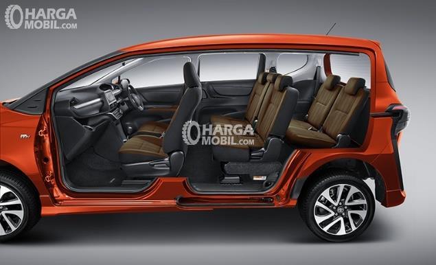 Gambar mobil Toyota Sienta 2016 berwarna orange dengan sisi samping terbuka dan bisa melihat kursi di dalamnya