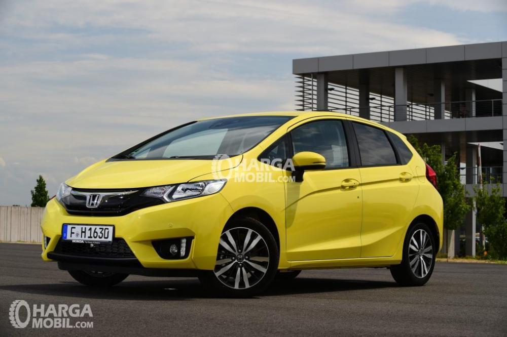 Tampilan bagian depan mobil Honda Jazz 2014 berwarna kuning sedang parkir di depan rumah