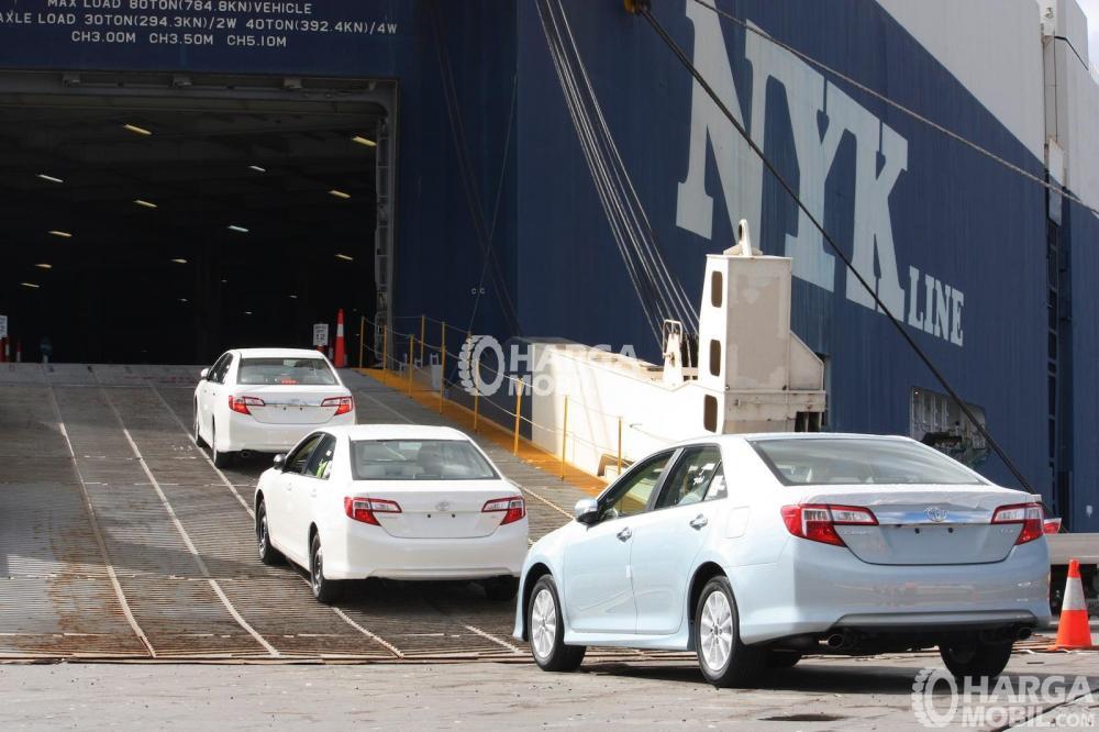 gambar menunjukkan tiga mobil sedan Toyota berwarna putih sedang berkendara di dalam kapal untuk siap diekspor