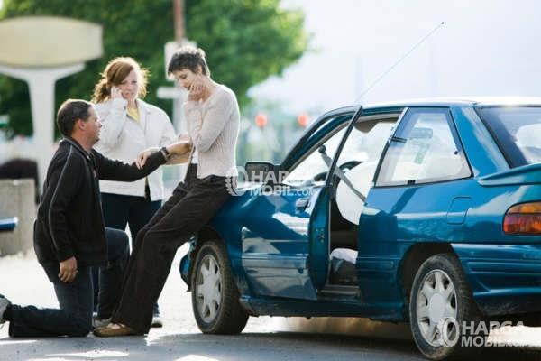 gambar menunjukkan seorang pria sedang memeriksa kondisi seorang wanita setelah terjadi kecelakkaan