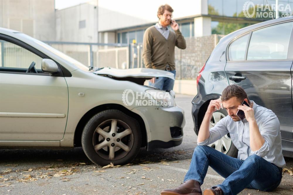 gambar menunjukkan dua orang pria sedang menelpon setelah terjadi kecelakkaan