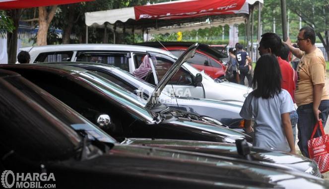 gambar menunjukkan banyak orang sedang memilih mobil bekas dalam sebuah dealer mobil