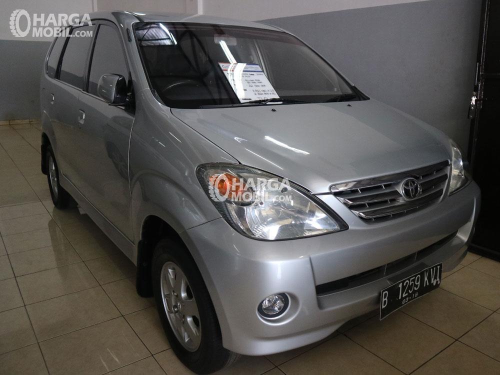 gambar menunjukkan sebuah mobil Toyota Avanza berwarna silver sedang diparkir dalam sebuah kamar