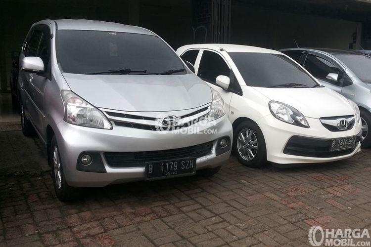 gambar menunjukkan dua mobil Daihatsu Xenia berwarna silver dan putih sedang diparkir di jalan