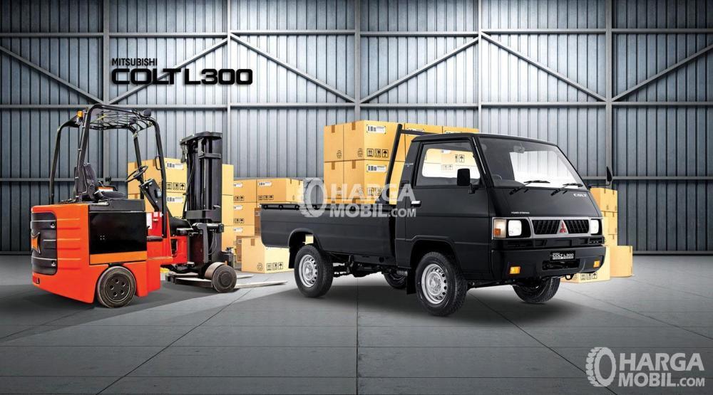 gambar menunjukkan sebuah mobil Mitsubishi Colt L300 berwarna hitam sedang ada dalam sebuah gudang