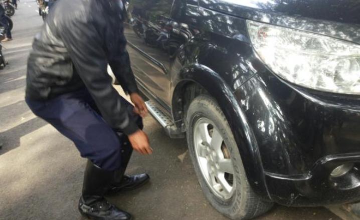 Gambar menunjukkan seorang pria sedang Memeriksa Kondisi Ban Mobil berwarna hitam